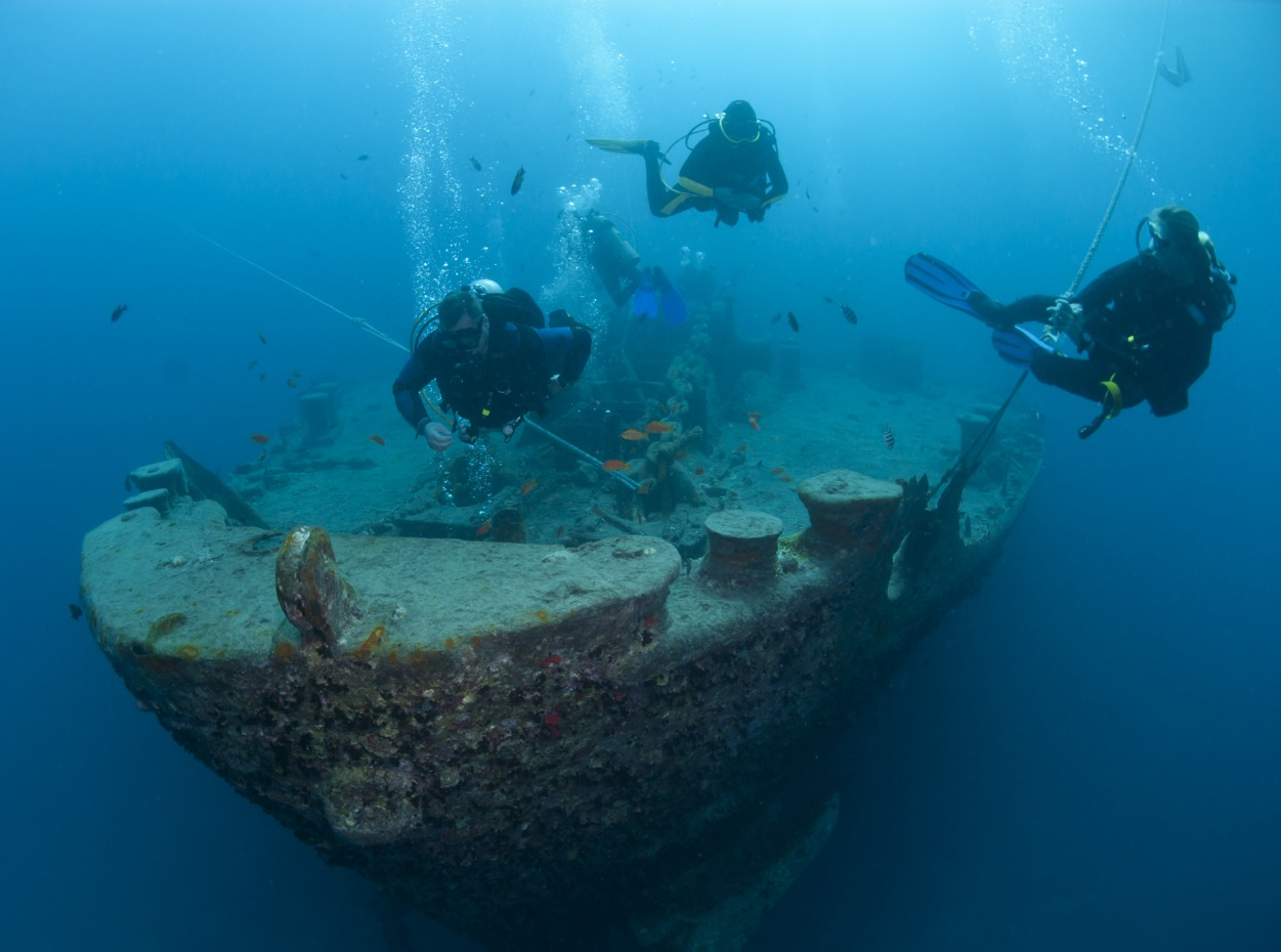 Three scuba divers swim away from the SS Thistlegorm wreck in the Red Sea