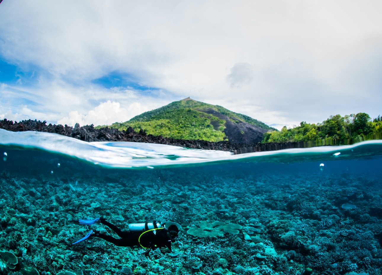 Scuba diver captured in under over photo in Indonesia with mountain backdrop